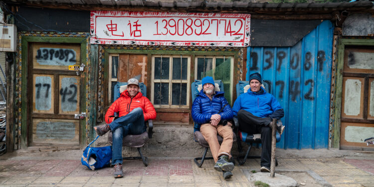 Jim Hurst, Thom Pollard, and Mark Synnott sit in Jilong shortly after crossing the border from Nepal. (National Geographic/Renan Ozturk)